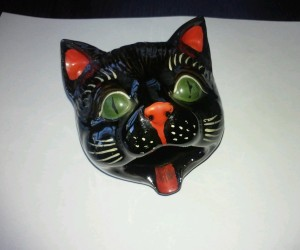 Ceramic ashtray painted and shaped like a cat's head.